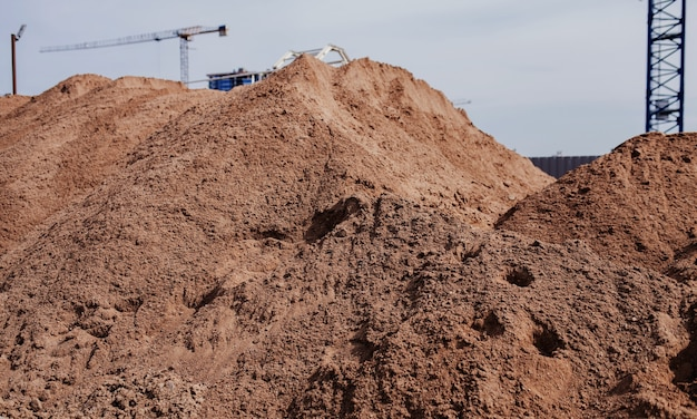 Een stapel zand op een bouwplaats. materiaal voor de productie van beton