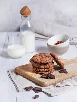 Een stapel zelfgemaakte chocoladekoekjes met chocoladeschilfers, noten en glas melk op een lichte lijst. vooraanzicht