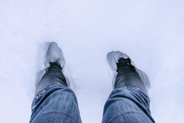 Een stappen in een diepe sneeuw. benen in spijkerbroek in een drift.