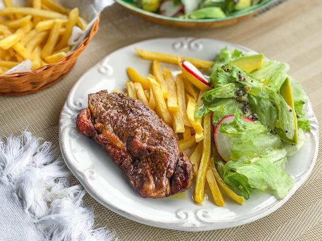 Een steak vergezeld van een vegan groene salade met avocado, radijs, sla en quinoa.