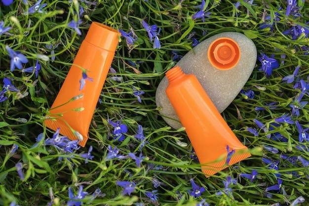 Een steen en twee tubes crème op een florale achtergrond. het concept van natuurlijke natuurlijke cosmetica.