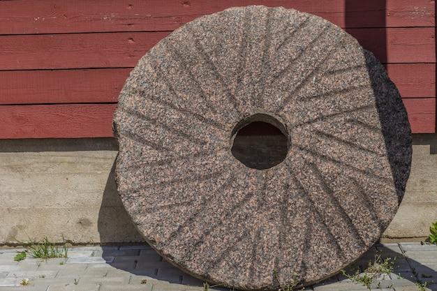 Een steencirkel staat bij een houten muur