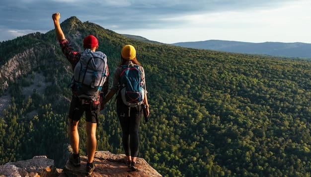Een stel bewondert de zonsondergang in de bergen van bashkiria. reizigers op de achtergrond van bergen, panorama. mensen bij zonsondergang in de bergen. reizigers met rugzakken op de achtergrond van de natuur