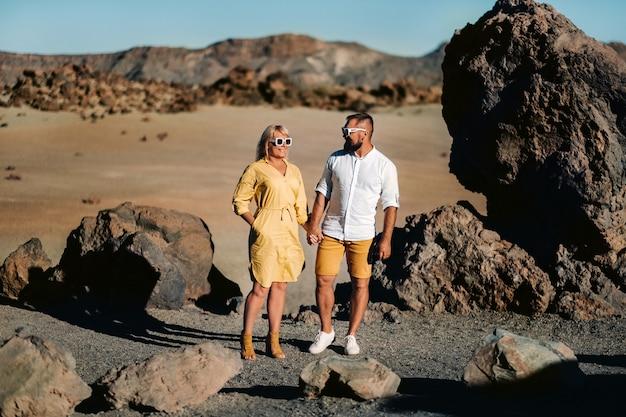 Een stel, een vrouw en een man in de woestijnkrater van de vulkaan teide en genieten van het uitzicht op de zonsondergang. reis naar de bergen, vrijheid en het concept van een actieve levensstijl. canarische eilanden, spanje.