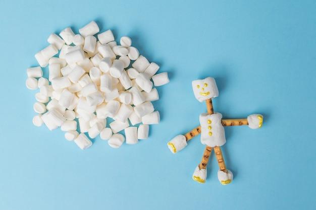 Een stel kleine marshmallows en een man. een collage van snoepjes. plat leggen.
