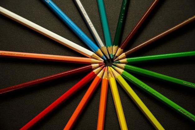 Een stel kleurrijke potloden raken elkaars hoofden aan