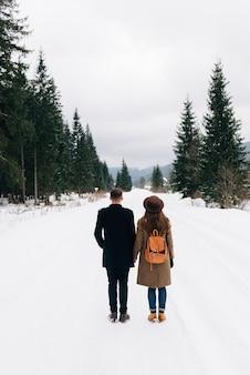 Een stel loopt door het winterbos, uitzicht vanaf de achterkant