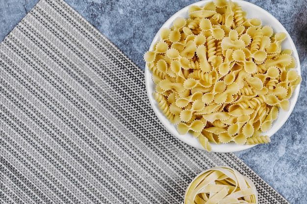 Een stelletje ongekookte pasta op marmer.
