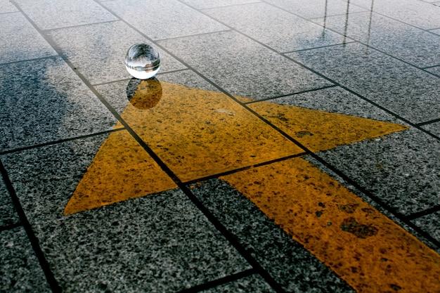 Een stenen grond met een gele pijl die naar kristallen bal wijst