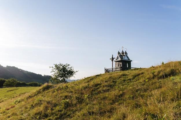 Een stenen kapel op een weide van bergen op een achtergrond van blauwe hemel. karpaten. oekraïne. oost-europa.