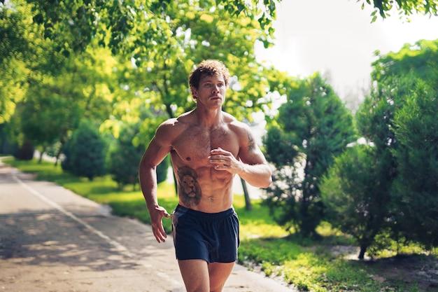 Een sterke, aantrekkelijke man die zonder shirt buiten in het park rent
