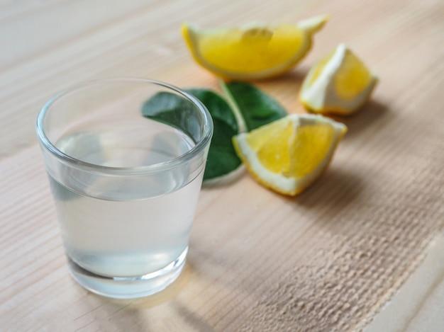 Een sterke alcoholische drank grappa met citroen op een lichte houten tafel.