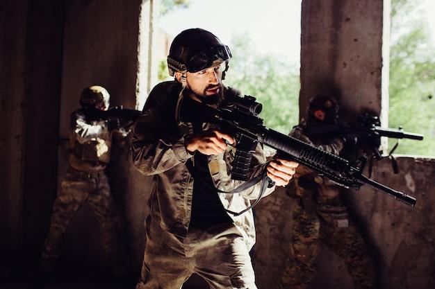 Een sterke en goedgebouwde soldaat staat met zijn tegenstanders in de donkere kamer en bewaakt deze.