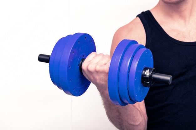 Een sterke gespierde arm houdt een halter vast. afgezwakt.
