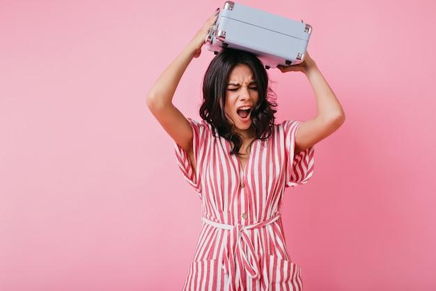 Een sterke jonge vrouw tilde haar koffertje boven haar hoofd en schreeuwde. portret van stijlvol model met emotionele gezichtsuitdrukking.