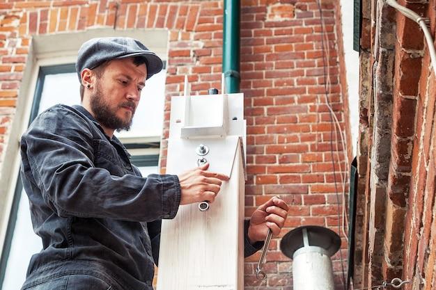 Een sterke mannelijke bouwvakker in een bouwzwarte overall en een dop draait een moer op een witmetalen structuur op straat vast met een moersleutel