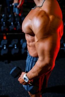 Een sterke, volwassen, fitte, gespierde mannelijke trainer poseert voor een fotoshoot in een sporthal onder de schijnwerpers in sportkleding, demonstreert zijn spieren en houdt zelfverzekerd dumbbells vast.