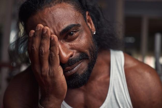 Een sterke zwarte man met een baard, lang haar en een oorbel in zijn oor kijkt in de camera en glimlacht...