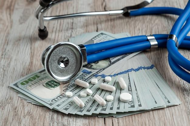 Een stethoscoop ligt op een bundel van geld en pillen op een lichte houten tafel