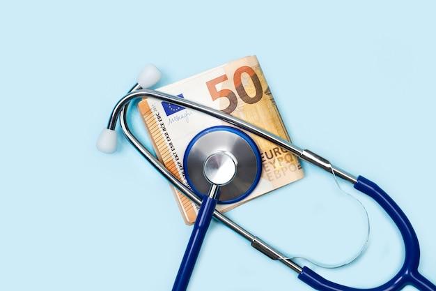 Een stethoscoop met een biljet van 50 euro op een lichtblauwe ondergrond
