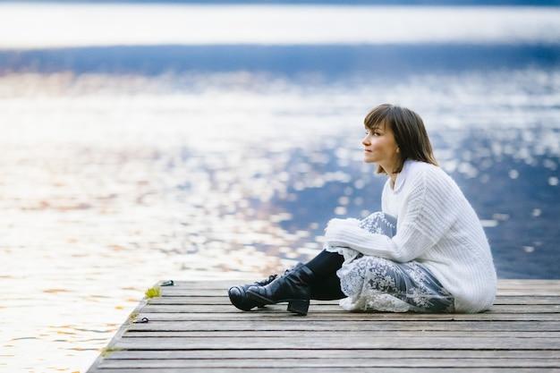 Een stijlvol en mooi meisje zit op een brug bij een groot meer