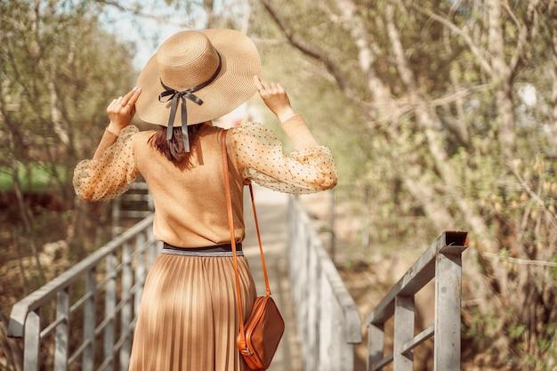 Een stijlvol gekleed meisje in een romantische beige jurk met een plooirok en een strohoed loopt over de brug.