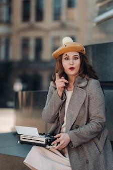 Een stijlvol jong mooi meisje zit en typt in de oude binnenstad van dresden, duitsland.
