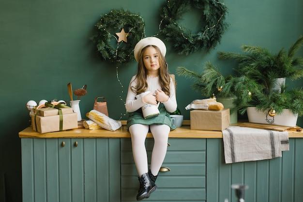 Een stijlvol meisje met een kruik in haar handen zit op het aanrecht in een keuken ingericht voor kerstmis en nieuwjaar in smaragdgroene en groene kleuren.