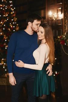 Een stijlvolle bebaarde man omhelst en kuste een jonge vrouw in een modieuze outfit bij kerstmis interieur