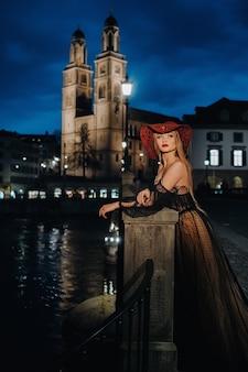 Een stijlvolle bruid in een zwarte trouwjurk en rode hoed poseert 's nachts in de oude stad van zürich. portret van een modelmeisje na zonsondergang. fotoshoot in zwitserland.