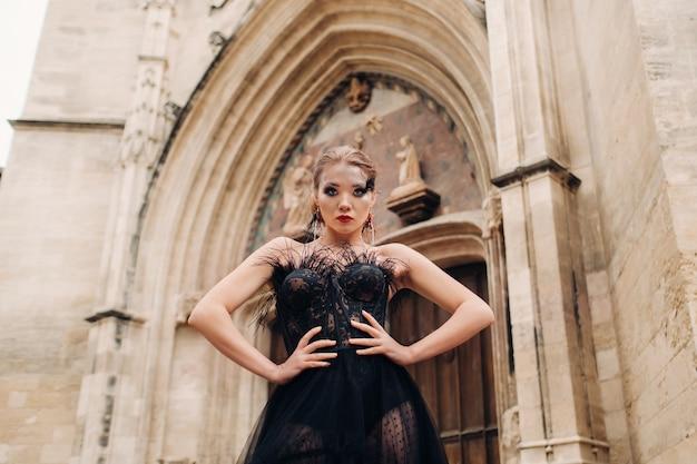 Een stijlvolle bruid in een zwarte trouwjurk poseert in de oude franse stad avignon. model in een zwarte jurk. het pauselijk paleis in avignon, provence.