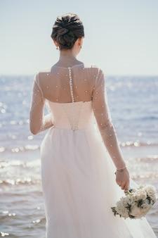 Een stijlvolle bruid staat met haar rug prachtig bruidsboeket in de handen van de bruid mooie en...