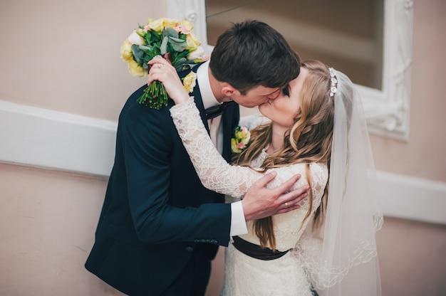 Een stijlvolle elegante bruid met een boeket bruiloft bloemen staat bij de spiegel op de trap bij muur. kussen de bruidegom in de lippen. knuffels. detailopname. portret. retro. vintage architectuur binnenshuis.