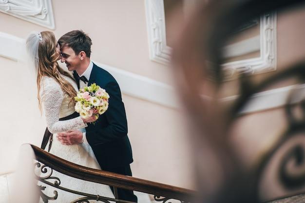Een stijlvolle elegante bruid met een boeket bruiloft bloemen staat bij de spiegel op de trap bij muur. kussen de bruidegom in het voorhoofd. knuffels. detailopname. portret. retro. vintage architectuur binnenshuis.