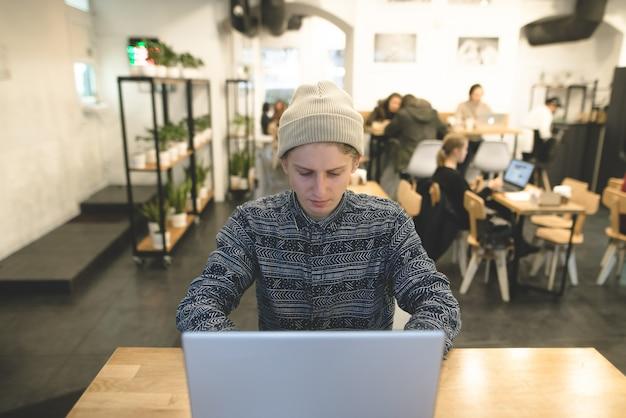 Een stijlvolle freelancer werkt voor een laptop in een gezellig café. een student zit aan een cafe tafel en met behulp van een laptop