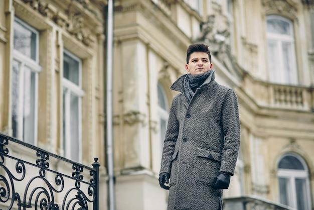 Een stijlvolle jonge man in een warme grijze jas en lederen handschoenen over oude historische gebouwen.