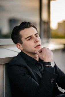 Een stijlvolle jonge man staat in de buurt van een gespiegeld gebouw tijdens zonsondergang. mode.