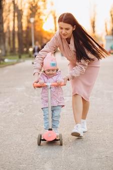 Een stijlvolle jonge moeder in roze kleding leert een dochtertje om op een scooter te rijden.