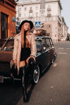 Een stijlvolle jonge vrouw in een beige jas en zwarte hoed op een straat in de stad zit bij zonsondergang op de motorkap van een auto