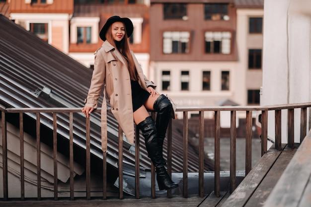 Een stijlvolle jonge vrouw in een beige jas en zwarte hoed zit op een dak in het stadscentrum. street fashion voor dames. herfstkleding. stedelijke stijl.