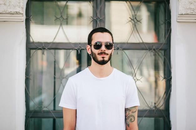 Een stijlvolle jongeman met een baard in een wit t-shirt en bril