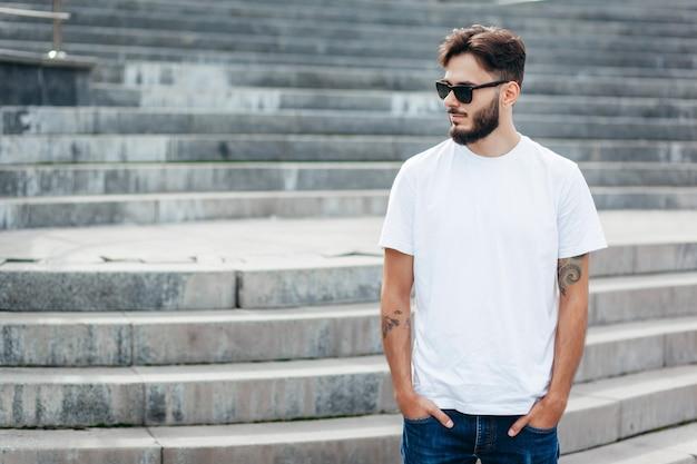 Een stijlvolle jongeman met een baard in een wit t-shirt en een bril