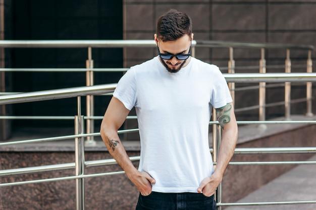 Een stijlvolle jongeman met een baard in een wit t-shirt en zonnebril