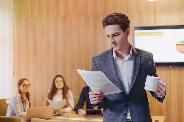 Een stijlvolle man in een jas en een shirt met een kopje koffie in zijn hand staat en leest documenten op de achtergrond van collega's op kantoor
