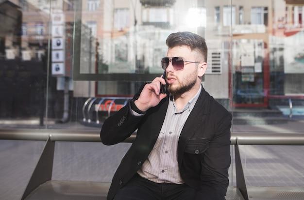 Een stijlvolle man in een kostuum spreekt telefonisch op een bankje van het openbaar vervoer.