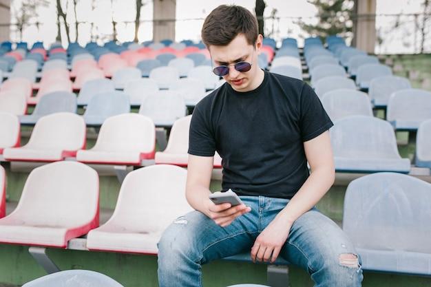 Een stijlvolle man in een zwart t-shirt gebruikt zijn smartphone