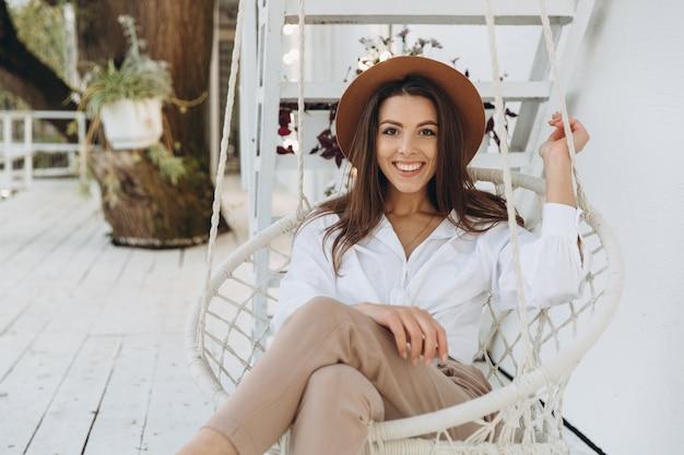 Een stijlvolle vrouw glimlachend en ontspannen in een club op het strand in warme zomerdag