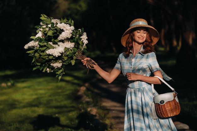 Een stijlvolle vrouw in een strohoed en een strozak poseert met een boeket van witte lila in een zonnig lentepark.