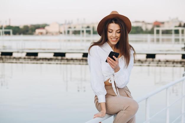 Een stijlvolle vrouw praten via de telefoon en wandelen langs het strand op een warme zomerdag bij zonsondergang