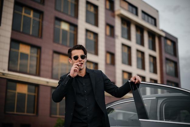 Een stijlvolle zakenman rookt sigaren in de buurt van een luxeauto. mode en zaken